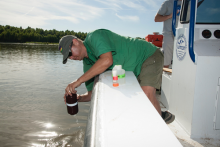Research collecting water samples from a boat.