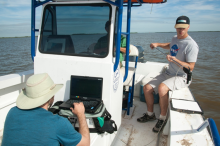 Researchers on a boat collecting data using an instrument.